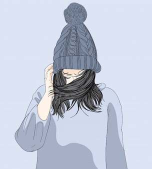 La niña llevaba un sombrero y su suéter en el invierno