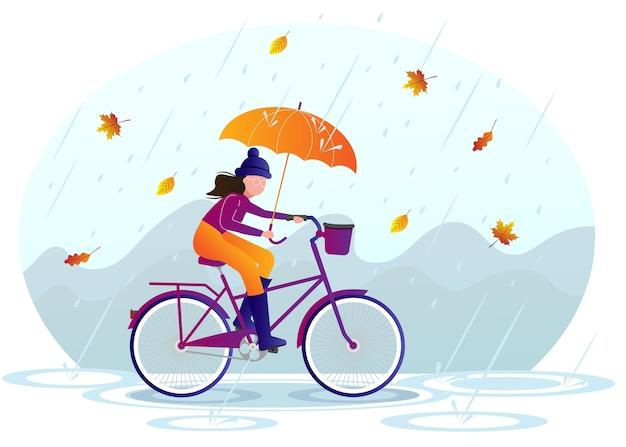 La niña monta una bicicleta bajo la lluvia. otoño
