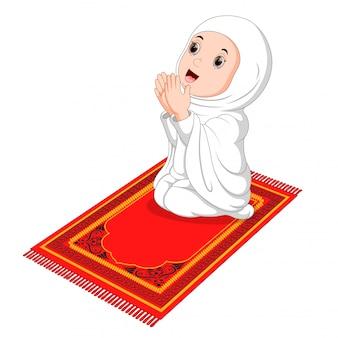 Niña musulmana sentada en la alfombra de oración mientras reza