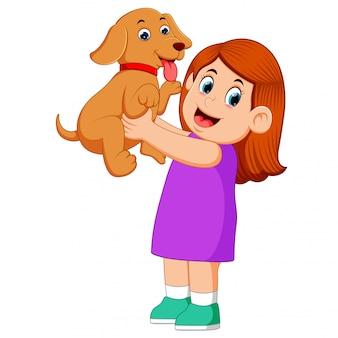 Una niña pequeña sostiene su nuevo cachorro marrón con la cara feliz.
