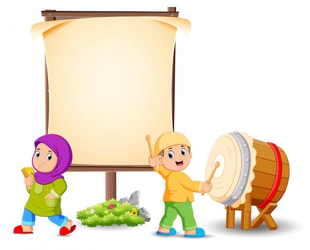 La niña está posando cerca del marco en blanco y el niño está golpeando el tambor