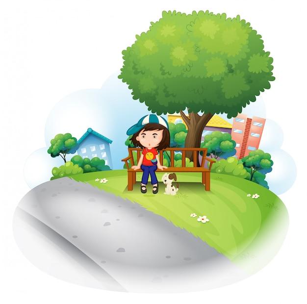 Una niña sentada en el banco de madera cerca del gran árbol