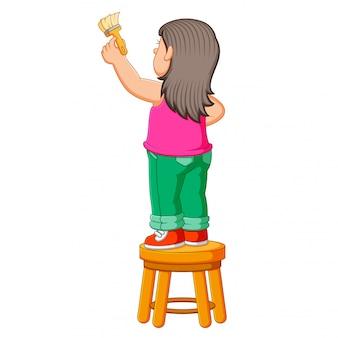 La niña está en la silla y sosteniendo el pincel para pintar.