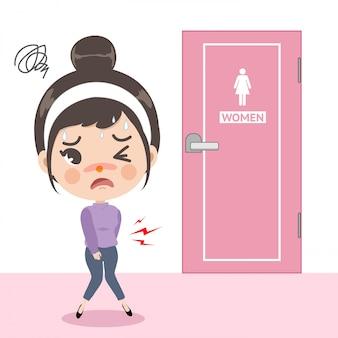 La niña sintió un dolor de estómago en frente del inodoro, pero está muy ocupada causando que sufra porque quería usar el inodoro de inmediato.