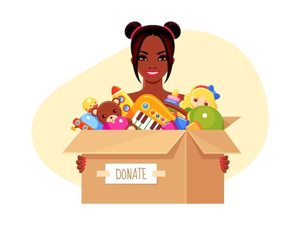 Niña sonriente sosteniendo una caja de papel de donación con juguetes para niños