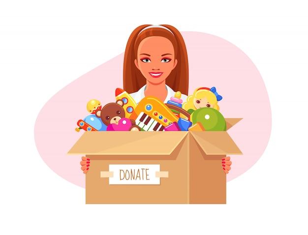 Niña sonriente voluntaria con caja de papel de donación con juguetes para niños