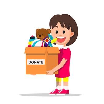 Niña sostiene una caja de cartón que contiene sus juguetes para donar
