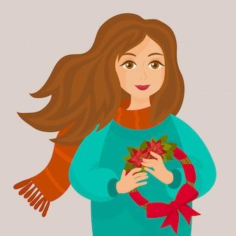 Una niña sostiene en sus manos una corona de navidad