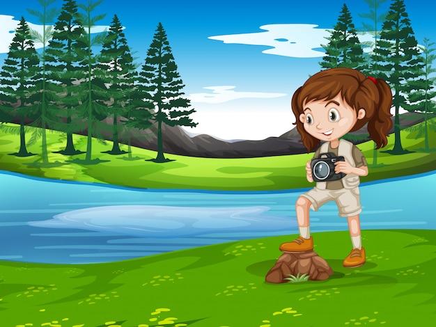 Una niña tomando fotos en la naturaleza.