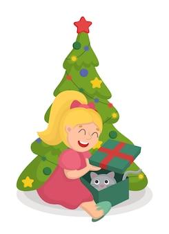 Una niña con un vestido rosa abre un regalo con un gato en una caja debajo del árbol de navidad.