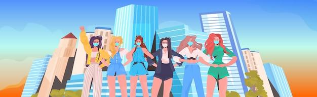 Niñas activistas en máscaras de pie juntas mujeres poder coronavirus concepto de cuarentena paisaje urbano retrato de fondo