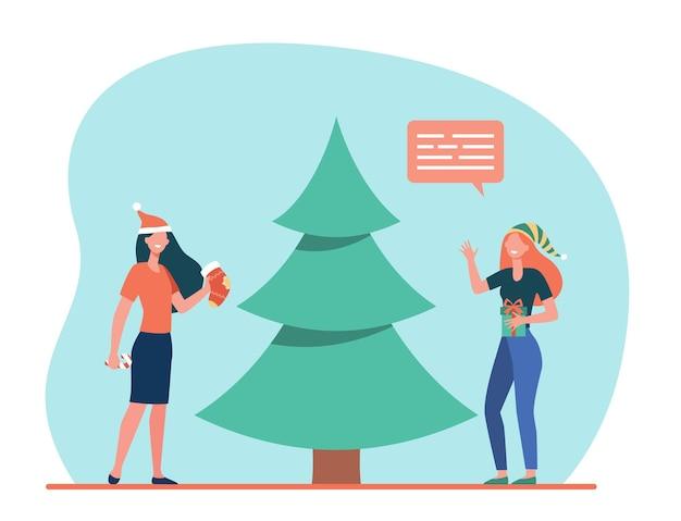 Niñas felices decorando el árbol de navidad