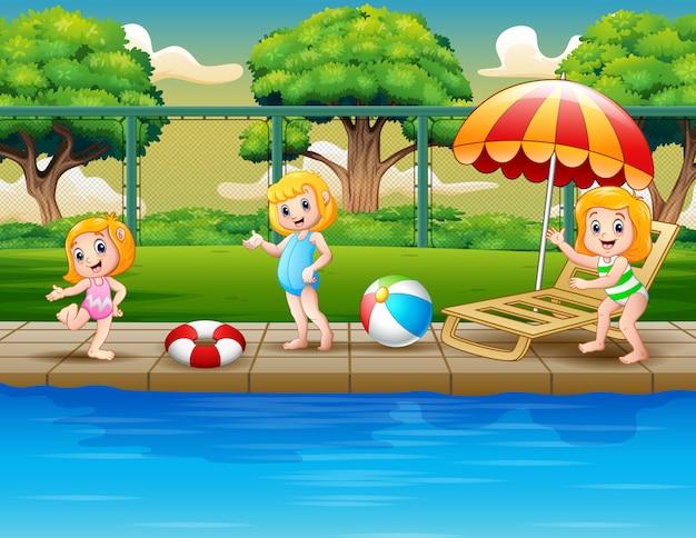 Niñas felices de dibujos animados jugando en la piscina