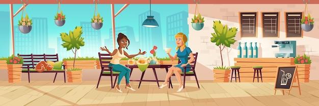 Niñas sentadas en la terraza de la cafetería o en el balcón con barra de bar de madera y plantas. interior de dibujos animados del patio de la cafetería con mesas, sillas y banco con gato durmiendo. las mujeres beben té y hablan