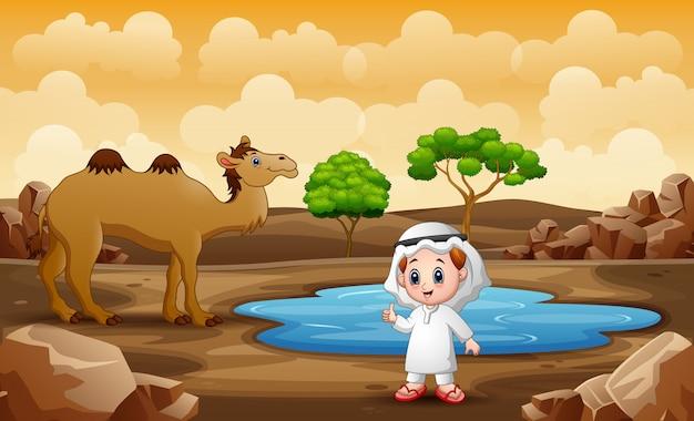 Niño árabe y camello junto al pequeño estanque