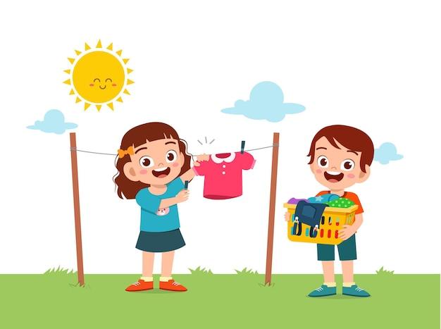Niño ayudando a hacer las tareas del hogar y secar la ropa afuera