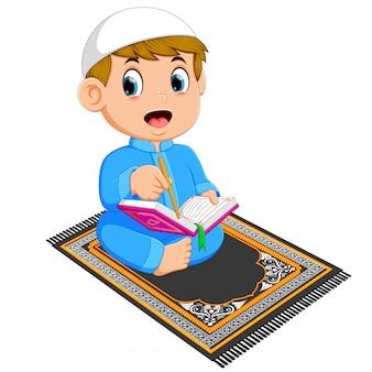 El niño con el caftán azul está leyendo el corán al en la alfombra de oración.