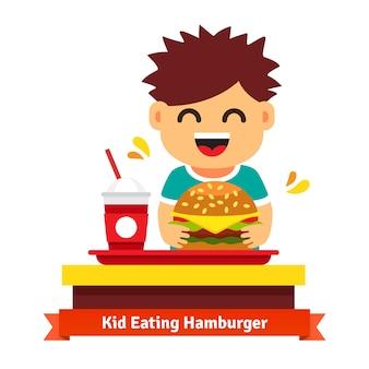 Niño comiendo y bebiendo en la mesa de comida rápida