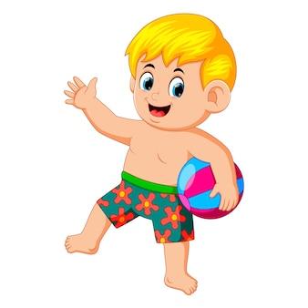 Niño con pelota de playa disfrutando de sus vacaciones