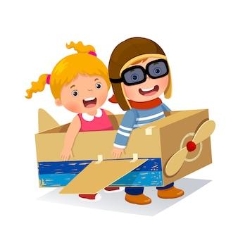 Niño creativo jugando como piloto con avión de cartón.