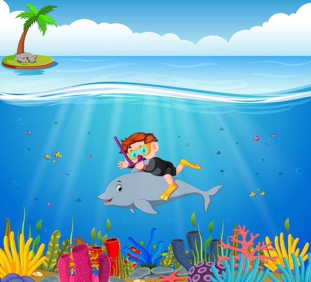 Niño de dibujos animados de buceo en el mar con delfines
