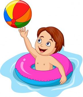 Niño de dibujos animados jugando un círculo inflable con una pelota de playa
