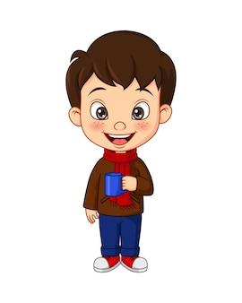 Niño de dibujos animados en ropa de otoño sosteniendo la taza
