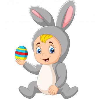 Niño de dibujos animados con traje de conejito de pascua sosteniendo un huevo de pascua