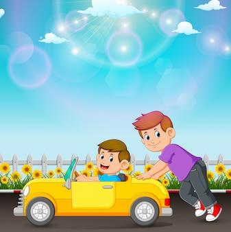 El niño está empujando el auto de su amigo en la carretera.
