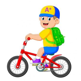 El niño va a la escuela con la bicicleta roja.