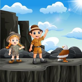Niño explorador dos en el acantilado con un pájaro