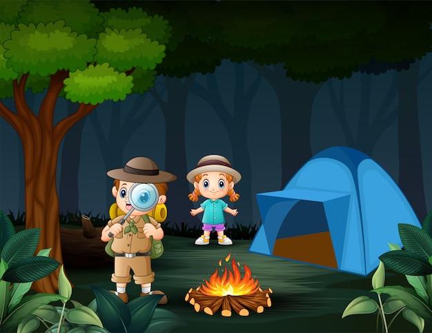 Niño explorador con lupa con una niña en el bosque