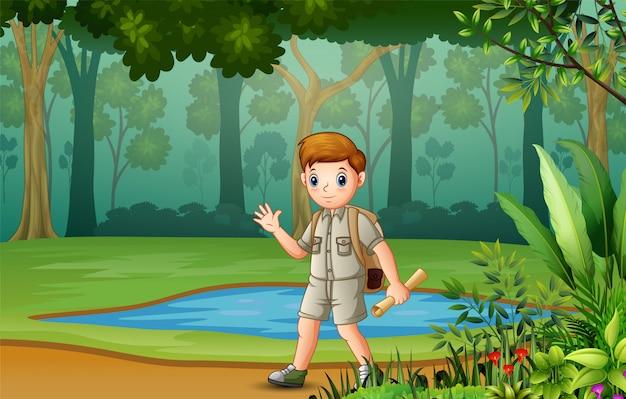 El niño explorador a través del bosque con mapas