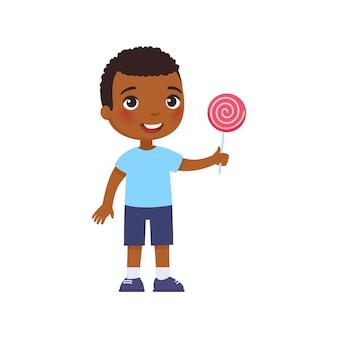 Niño feliz africano sonríe y sostiene una paleta rosada en su mano. personaje de piel oscura de dibujos animados