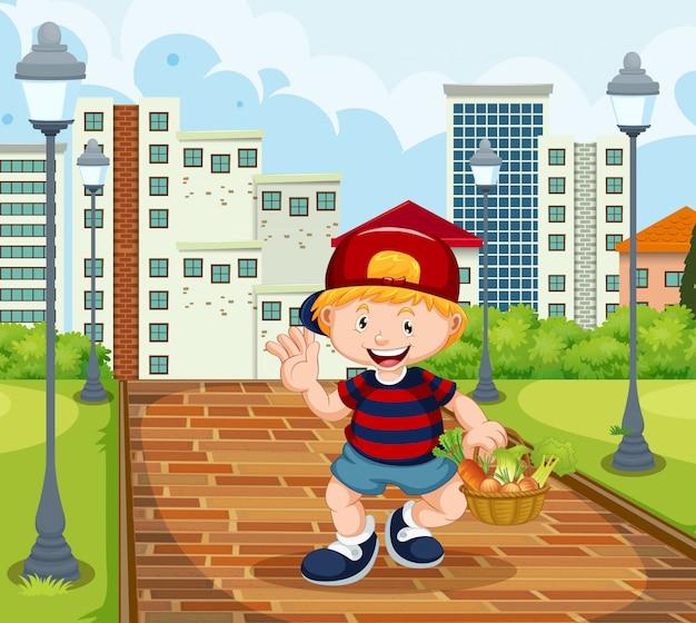 Niño feliz con cesta de vegetabale en el parque