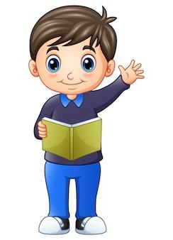 Niño feliz de pie y sosteniendo un libro