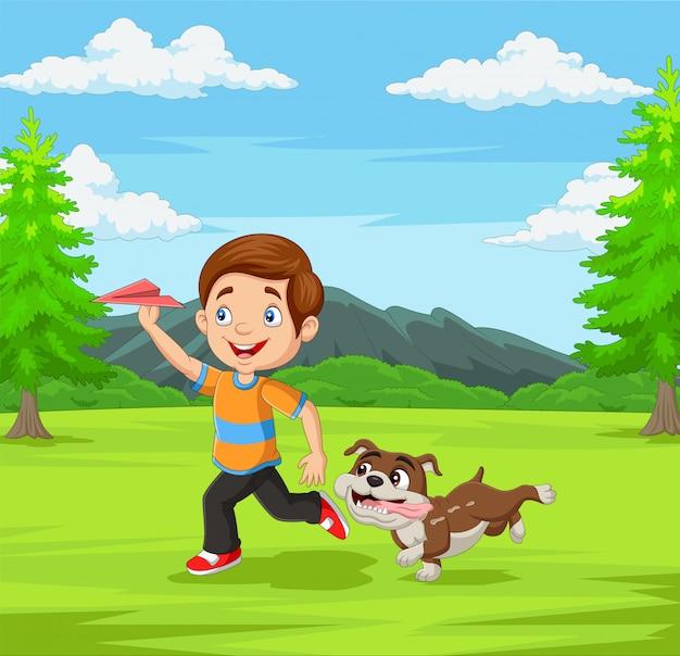 Niño feliz jugando avión de papel con su mascota en el parque