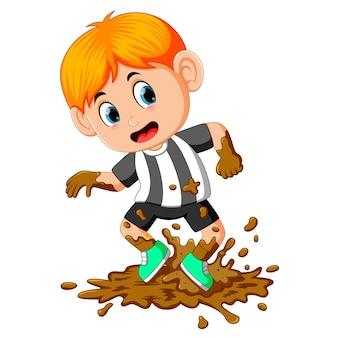 Niño feliz jugando en el barro