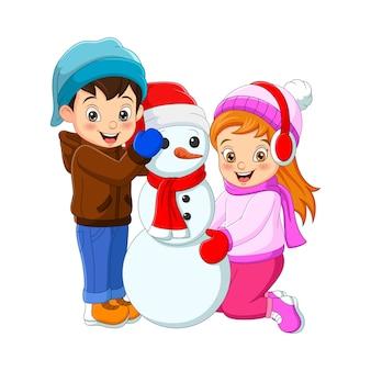 Niño feliz y niña jugando con un muñeco de nieve