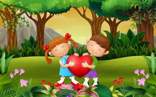 Niño feliz de la pareja de la historieta que lleva a cabo un corazón en el parque