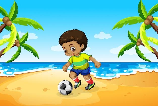 Un niño jugando al fútbol en la playa.