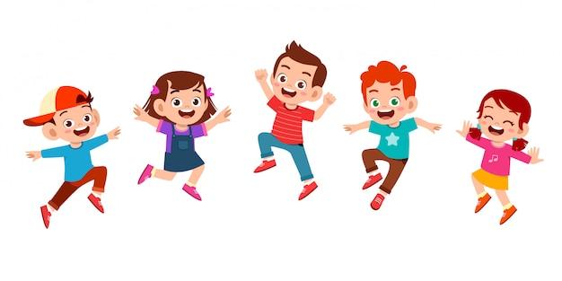 Niño lindo feliz salta con un conjunto de amigos