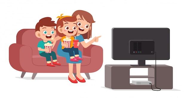Niño lindo feliz ver televisión con familia juntos