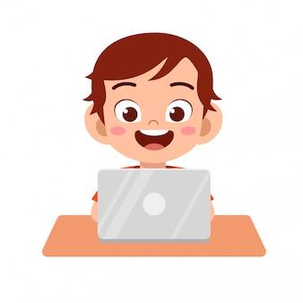 Niño lindo niño feliz usando la computadora portátil para hacer la tarea