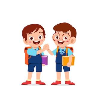 Niño lindo niño de la mano con su amigo