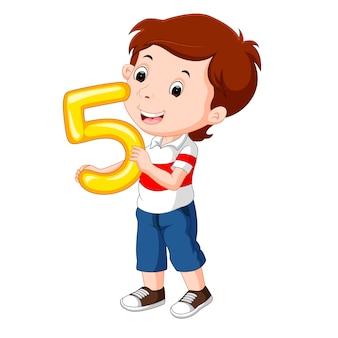 Niño lindo que sostiene el globo con el número cinco