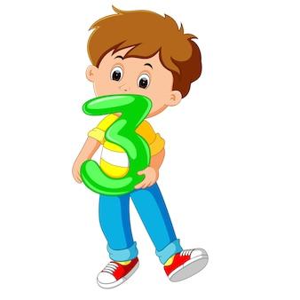 Niño lindo que sostiene el globo con el número tres