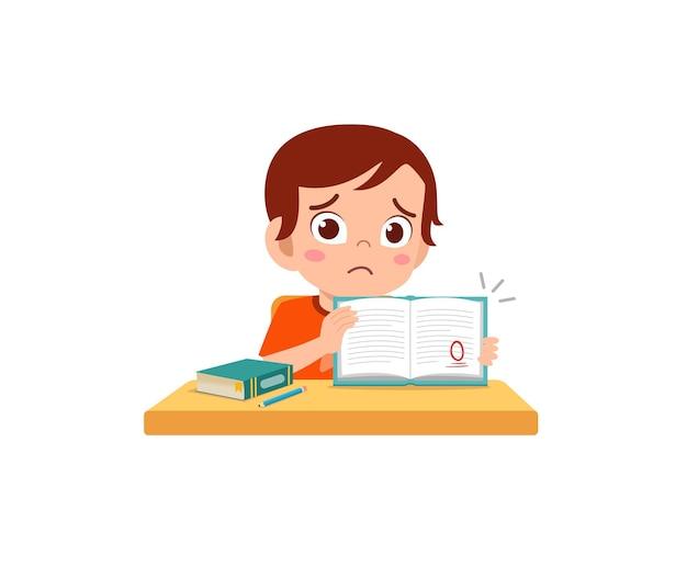 Niño lindo se siente triste porque obtiene una mala calificación en el examen