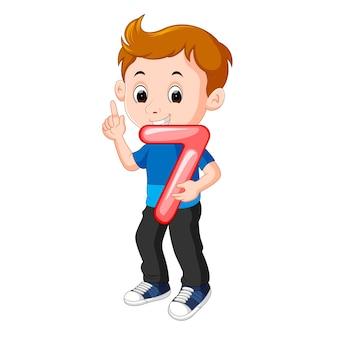 Niño lindo sosteniendo globo con el número siete