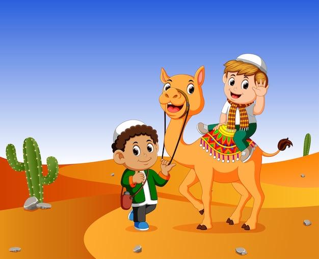 Un niño se mete en un camello en el desierto y los hombres guían al camello.